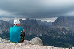 A man pausing after a via ferrata climb on top of Averau mountain peak, in Dolomites, Italy, gazing at the incoming storm. Clouds royalty free stock photos