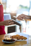 Man paying bill through smartphone using NFC technology. In cafe Stock Photography