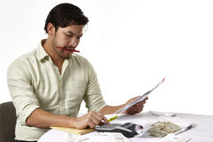 Man paying bills. Asian American man in his thirties paying bills. isolated. Worried about bankruptcy and how to make ends meet Royalty Free Stock Photography