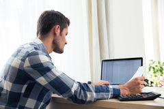 Man paying bills with his laptop Royalty Free Stock Photography