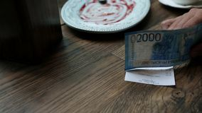 Man paying cash for bill in cafe. Paper money banknotes in man`s hand with restaurant check on the wooden table. Man paying cash for bill in cafe. Paper money stock footage