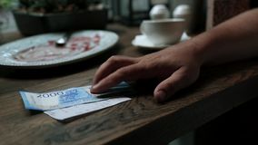 Man paying cash for bill in cafe. Paper money banknotes in man`s hand with restaurant check on the wooden table. Man paying cash for bill in cafe. Paper money stock video footage