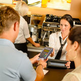 Man paying with credit card at cafe. Women service cashier Royalty Free Stock Images