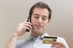 Man paying with credit card on phone Stock Photography