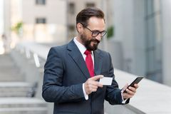Man paying with credit card on smart phone outside. Mature businessman making order with credit card an phone while walking royalty free stock image