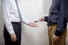 Man Paying a Dollars Bribe to a Corupted Nan Accepting It. Corrupted man paying a Dollars banknotes bribe to a businessman, or politician, accepting corruption royalty free stock photos