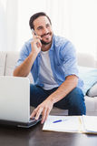 Man paying his bills with laptop while talking on phone Stock Image