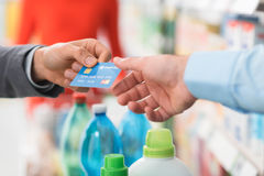 Man paying with his credit card. Man doing grocery shopping at the supermarket and paying with a credit card at the store checkout Royalty Free Stock Image