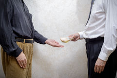 Man Paying a Hryvnia Bribe to a Corupted Nan Accepting It. Corrupted businessman, or politician, paying a Hryvnia banknotes bribe to a man accepting corruption stock images
