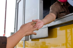 Man paying money at toll booth Stock Photos