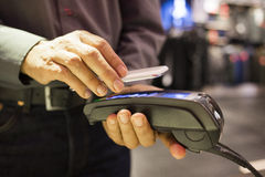 Man paying with NFC technology on mobile phone, in clothing stor Stock Image