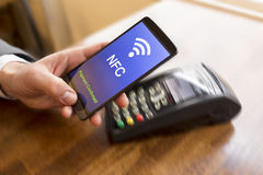 Man paying with NFC technology on mobile phone. Motion hand Stock Photo