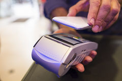 Man paying with NFC technology on mobile phone, in pharmacy Royalty Free Stock Images