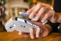 Man paying with NFC technology on mobile phone, in restaurant, b Stock Photos