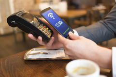 Man paying with NFC technology on mobile phone, in restaurant Royalty Free Stock Images