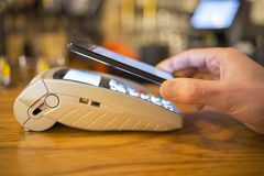 Man paying with NFC technology on mobile phone, restaurant, shop Royalty Free Stock Photography