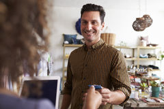Man paying sales assistant with credit card in clothes shop Royalty Free Stock Photos