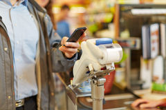 Man paying with smartphone at supermarket checkout. Man paying wireless with his smartphone at supermarket checkout stock image