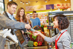 Man paying at supermarket checkout. Smiling men paying groceries at supermarket checkout with Euro money bill royalty free stock photos