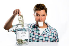 Man paying a swear jar. A man paying into a swear jar with a bar of soap in his mouth Stock Photos