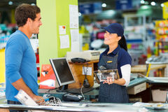 Man paying till point. Young men paying at till point in hardware store Royalty Free Stock Photos