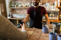 Man with payment terminal and hand with smartphone. Modern technology and people concept - man or bartender with payment terminal and customer hand with Royalty Free Stock Photography