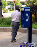 Man on payphone. The last person on earth without a cell phone royalty free stock photography