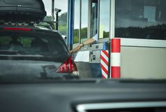 A man pays money to a cashier for a toll road Stock Images