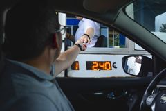A man pays money to a cashier for a toll road. Toll gate motorway entrance royalty free stock photography