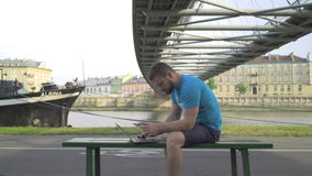 Man pays online using credit card. Man pays online using credit card, sitting on the bench against the river and old town. Above, there is a footbridge. He is stock video