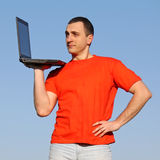 Man with PC. Man in red t-shirt with laptop Royalty Free Stock Image