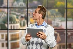 Man with pc tablet looking aside. Stock Image