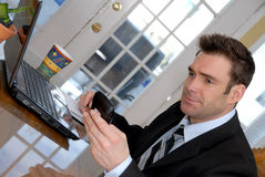 Man on the PDA. Businessman at his dining room table with PDA Stock Photography