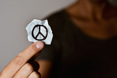 Man with a peace symbol in a piece of paper. Closeup of a young man showing a piece of paper with a peace symbol drawn in it stock images