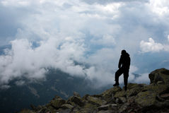 Man on the peak. Silhouette of a hiker on high grounds Stock Photos