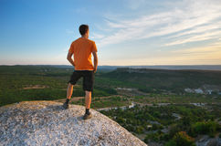 Man on peak of mountain Stock Images