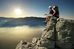 Man on peak of mountain stock photography