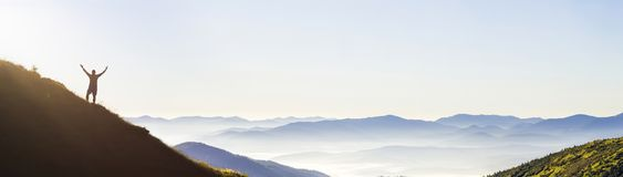 Man on peak of mountain. Emotional scene. Young man with backpack standing with raised hands on top of a mountain and enjoying mo. Untain view. Hiker on the royalty free stock photography