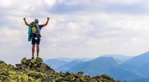 Man on peak of mountain. Emotional scene. Young man with backpack standing with raised hands on top of a mountain and enjoying mo. Untain view. Hiker on the stock images