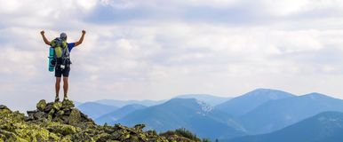 Man on peak of mountain. Emotional scene. Young man with backpac. K standing with raised hands on top of a mountain and enjoying mountain view. Hiker on the Stock Photography