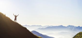 Man on peak of mountain. Emotional scene. Young man with backpack standing with raised hands on top of a mountain and enjoying mo. Untain view. Hiker on the stock photos