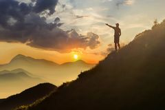 Man on peak of mountain. Emotional scene. Young man with backpack standing with raised hands on top of a mountain and enjoying mo. Untain view. Hiker on the stock photo