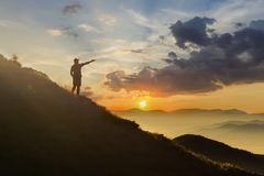 Man on peak of mountain. Emotional scene. Young man with backpack standing with raised hands on top of a mountain and enjoying mo. Untain view. Hiker on the royalty free stock images