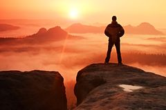 Man on peak of sandstone rock in national park Saxony Switzerland watching to Sun. Beautiful moment Royalty Free Stock Photos