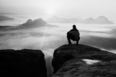 Man on peak of sandstone rock in national park Saxony Switzerland watching to Sun. Beautiful moment Royalty Free Stock Images