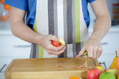 Man pealing apple with knife. A men pealing apple with knife Royalty Free Stock Photo