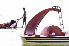 Man and pedalo at sea. A man on a raft passes near a pedal boat in the Mediterranean Sea Stock Photo