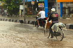 A man pedals a cycle used for transporting goods during a flash flood Royalty Free Stock Photos