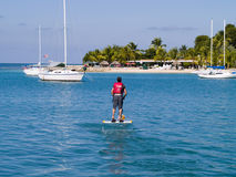 Man on peddle boat in tropics. A view of a man on a peddle boat making his way across a bay or marina toward an island beach on St. Croix, US Virgin Islands Royalty Free Stock Images
