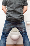 Man peeing standing up in the restroom Stock Photo